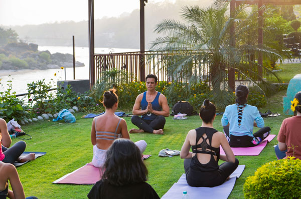 Yoga retreat in India Rishikesh Practicing on the banks of the Ganges river 1